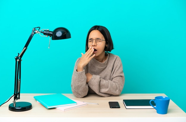 Jonge student gemengd ras vrouw die een tafel bestudeert die geeuwt en wijd open mond bedekt met de hand