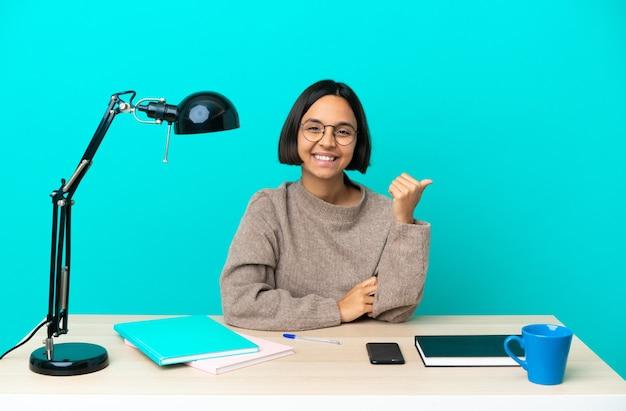 Jonge student gemengd ras vrouw die een tafel bestudeert die naar de zijkant wijst om een product te presenteren