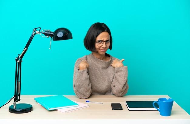 Jonge student gemengd ras vrouw die een tafel bestudeert die naar zichzelf wijst