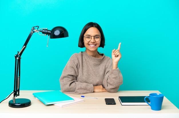 Jonge student gemengd ras vrouw die een tafel bestudeert en wijst op een geweldig idee