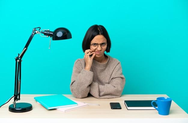 Jonge student gemengd ras vrouw die een tafel bestudeert met een teken van stilte gebaar