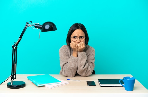 Jonge student gemengd ras vrouw die een tafel bestudeert, nerveus en bang om de handen in de mond te leggen