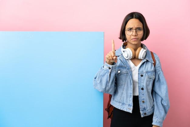 Jonge student gemengd ras vrouw met een grote banner geïsoleerde achtergrond die er een telt met serieuze uitdrukking