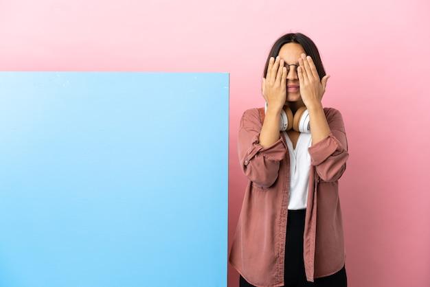Jonge student gemengd ras vrouw met een grote banner geïsoleerde achtergrond die ogen bedekt door handen