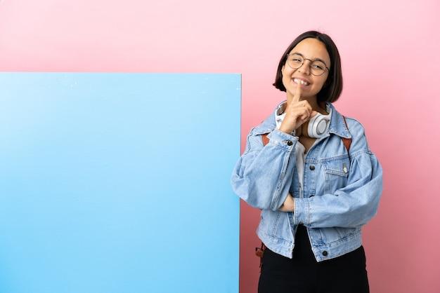 Jonge student gemengd ras vrouw met een grote banner geïsoleerde achtergrond met een teken van stilte gebaar vinger in mond zetten