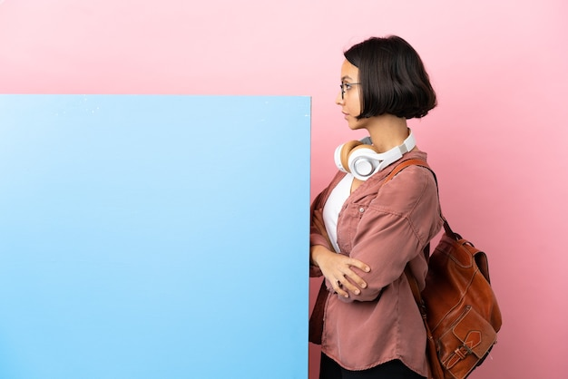Jonge student gemengd ras vrouw met een grote banner over geïsoleerde achtergrond in zijpositie