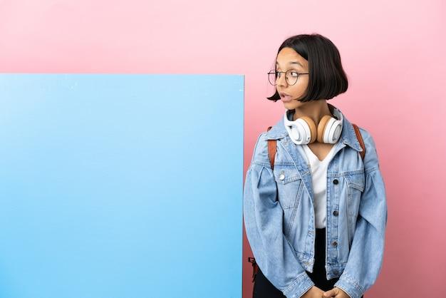Jonge student gemengd ras vrouw met een grote banner over geïsoleerde achtergrond. portret