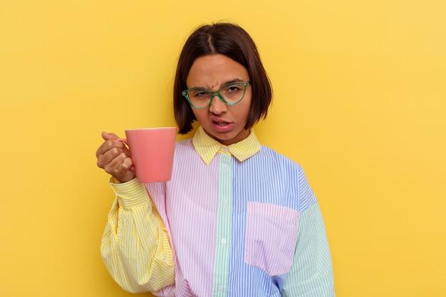 Jonge student gemengd ras vrouw met een zelfvoldane geïsoleerd op gele muur