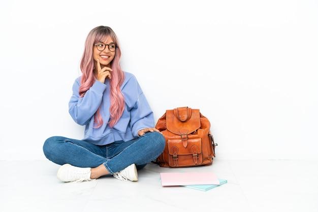 Jonge student gemengd ras vrouw met roze haar zittend op de vloer geïsoleerd op een witte achtergrond denkend aan een idee terwijl ze omhoog kijkt