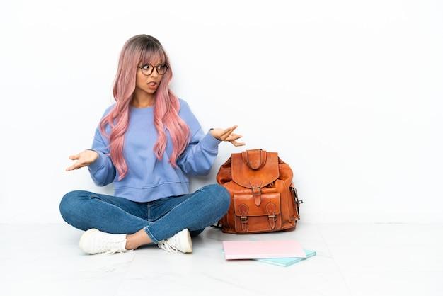 Jonge student gemengd ras vrouw met roze haar zittend op de vloer geïsoleerd op een witte achtergrond met verrassing gezichtsuitdrukking