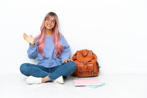 Jonge student gemengd ras vrouw met roze haar zittend op de vloer geïsoleerd op een witte achtergrond saluerend met de hand met gelukkige uitdrukking