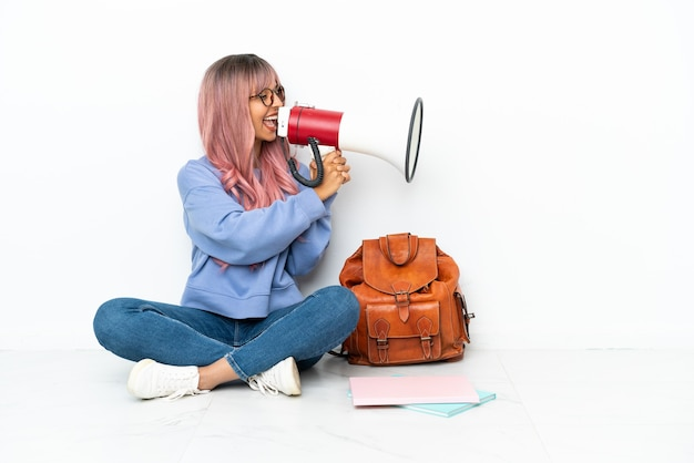 Jonge student gemengd ras vrouw met roze haar zittend op de vloer geïsoleerd op een witte achtergrond schreeuwend door een megafoon