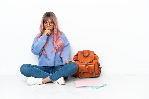 Jonge student gemengd ras vrouw met roze haar zittend op de vloer geïsoleerd op een witte achtergrond verrast en geschokt terwijl ze naar rechts kijkt