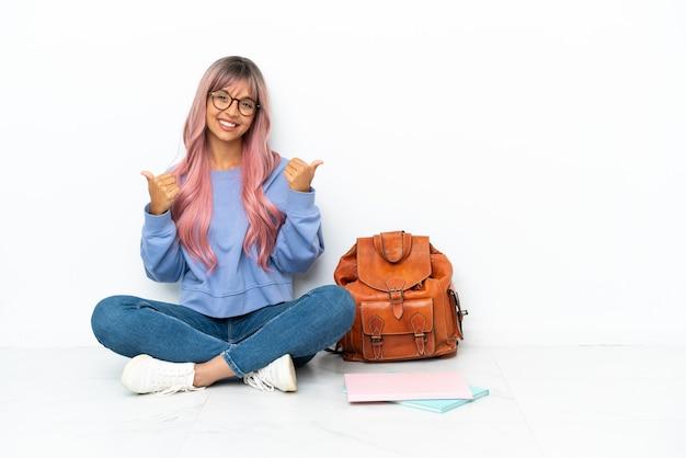 Jonge student gemengd ras vrouw met roze haren zittend op de vloer geïsoleerd op een witte achtergrond met duim omhoog gebaar en lachend
