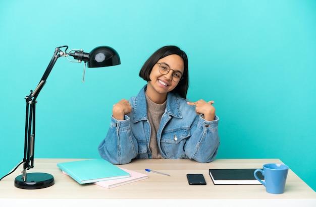 Jonge student gemengd ras vrouw studeren aan een tafel trots en zelfvoldaan