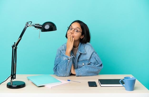 Jonge student gemengd ras vrouw studeren op een tafel die de mond bedekt met de hand