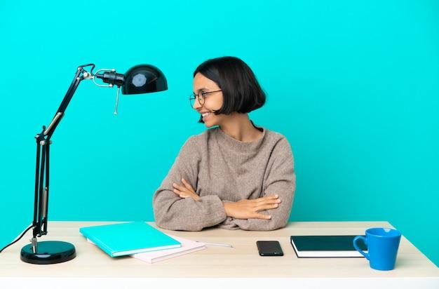 Jonge student gemengd ras vrouw studeren op een tafel in zijpositie