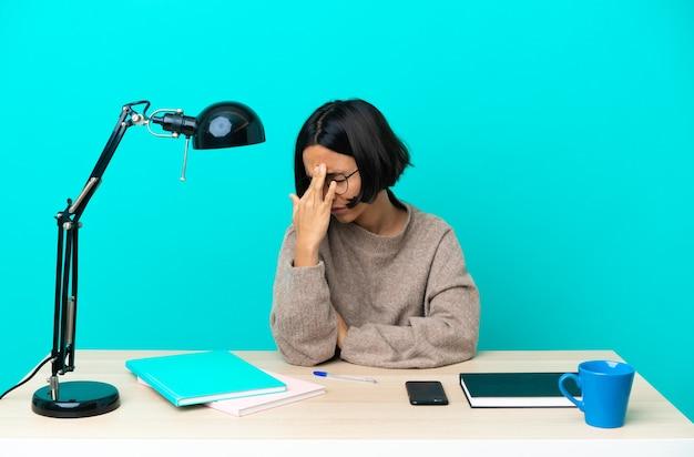 Jonge student gemengd ras vrouw studeren op een tafel met hoofdpijn