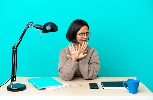 Jonge student gemengd ras vrouw studeren op een tafel stopgebaar maken met haar hand om een act te stoppen