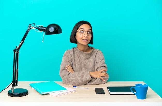 Jonge student gemengd ras vrouw studeren op een tafel terwijl ze glimlachend omhoog kijkt