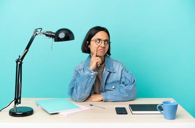 Jonge student gemengd ras vrouw studeren op een tafel twijfels tijdens het opzoeken