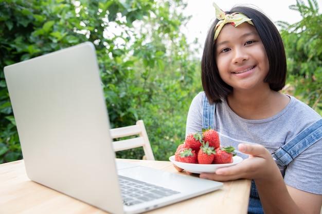 Jonge student hield een groep aardbeien in haar gerecht na het oogsten van de ranch. ze eten graag fruit terwijl ze online studeren in de voortuin. onderwijs van thuis uit. bescherm coronavirus.