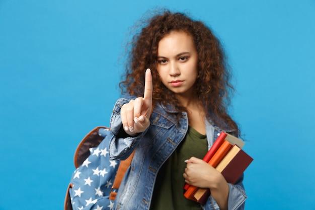 Jonge student in denim kleding en rugzak houdt boeken geïsoleerd op blauwe muur