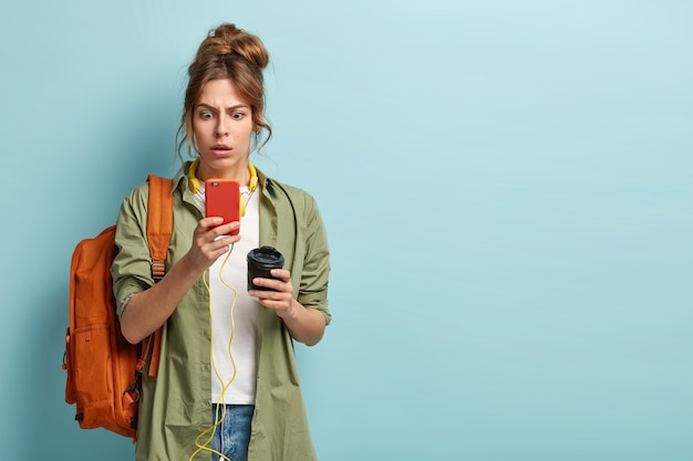 Jonge student in verlegenheid gebracht met gekamd haar, draagt casual shirt, verrast door slechte internetverbinding, staart naar scherm van mobiele telefoon, downloadt muziek in afspeellijst, drinkt afhaalkoffie