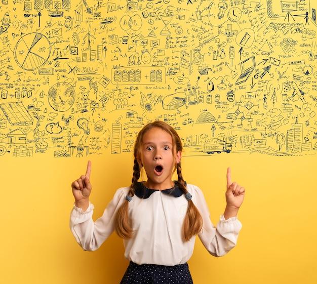 Jonge student is met een geschokte uitdrukking en wijst op een complexe oefening. gele achtergrond