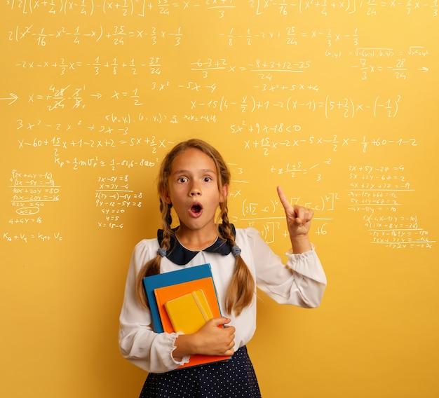 Jonge student is met geschokte uitdrukking en wijst op een complexe formule