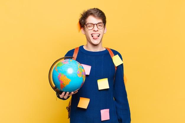Jonge student jongen met vrolijke, zorgeloze, rebelse houding, grappen maken en tong uitsteken, plezier maken