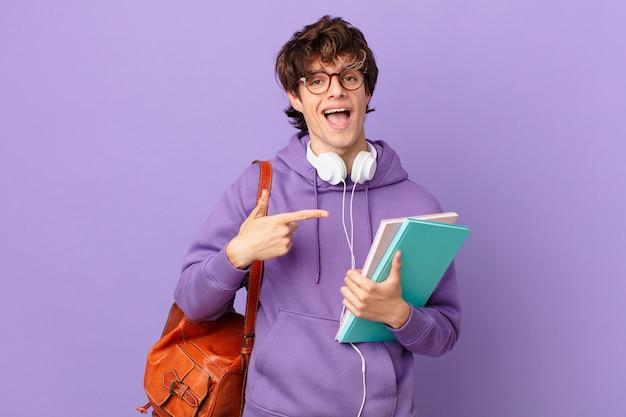 Jonge student man die opgewonden en verrast kijkt en naar de zijkant wijst