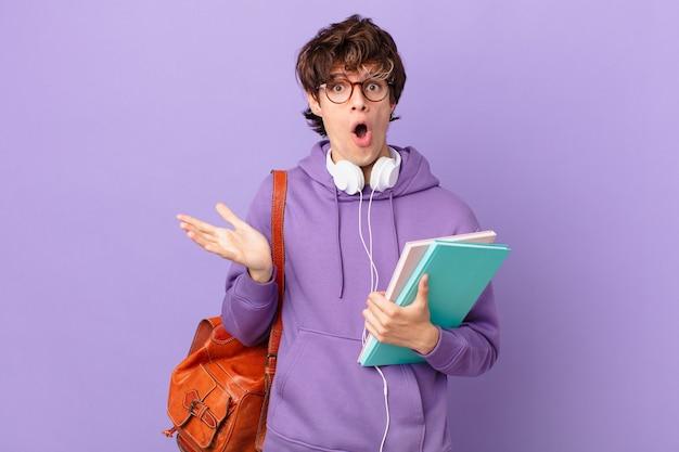 Jonge student man voelt zich extreem geschokt en verrast Premium Foto