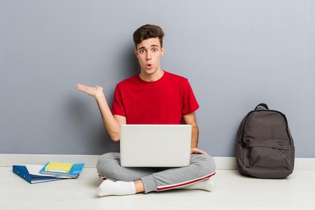 Jonge student man zittend op zijn huisvloer met een laptop