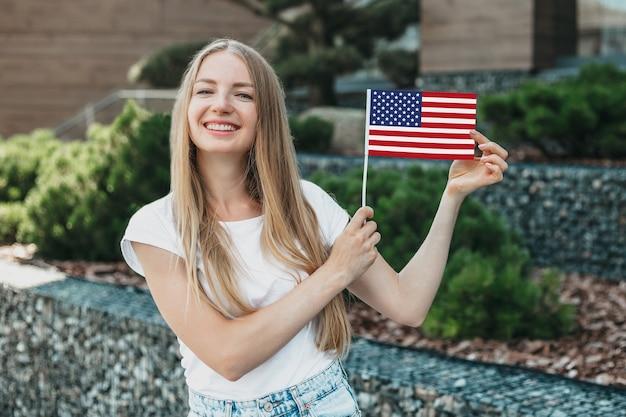 Jonge student meisje lacht en toont een kleine amerikaanse vlag en staat tegen de achtergrond van de universiteit