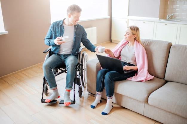Jonge student met een handicap zorgen voor vriendin. man met speciale behoeften. ze zit op de bank en houdt laptop vast. man geeft haar kopje koffie. studenten samen.