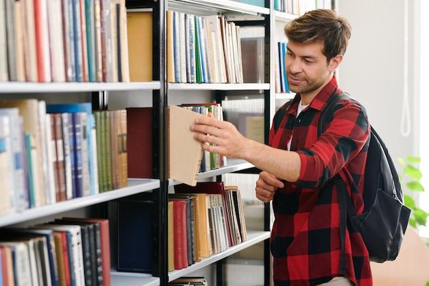 Jonge student met rugzak die een van de boeken uit de plank neemt tijdens een bezoek aan de universiteitsbibliotheek