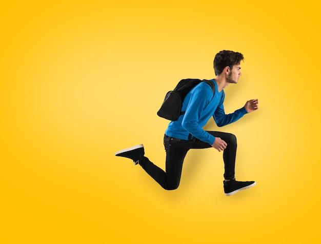 Jonge student met rugzak die op gele achtergrond wordt uitgevoerd