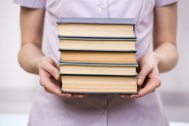 Jonge student met stapel boeken
