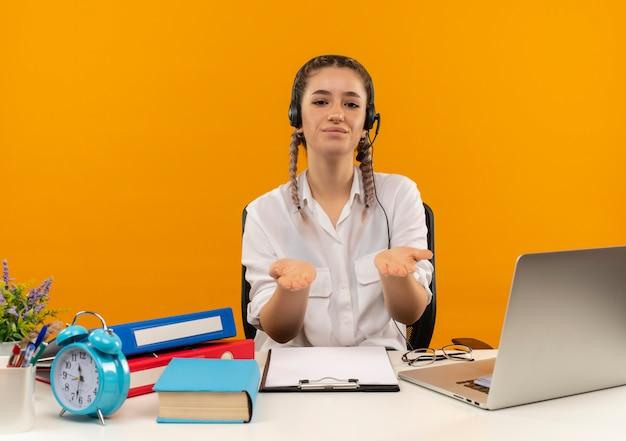 Jonge student met vlechten in wit overhemd en koptelefoon studeren