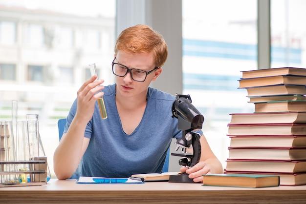 Jonge student moe en uitgeput voorbereidingen voor chemie examen