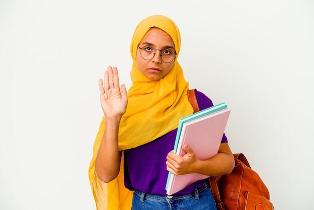 Jonge student moslimvrouw die een hijab op wit draagt ?? dat zich met uitgestrekte hand bevindt die stopbord toont, dat u verhindert.
