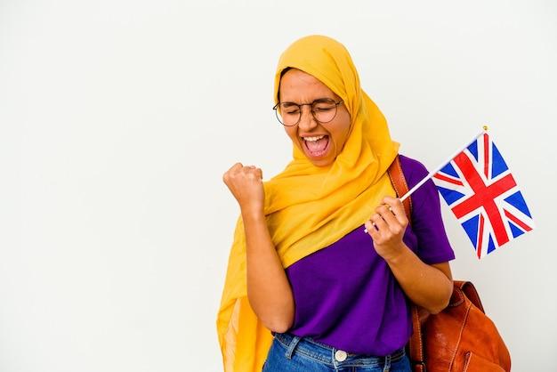 Jonge student moslimvrouw geïsoleerd op een witte achtergrond die vuist opheft na een overwinning, winnaar concept.