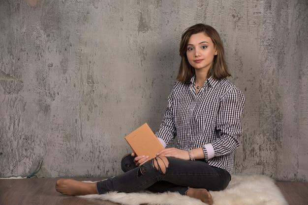 Jonge student poseren aan de voorkant met oranje boek