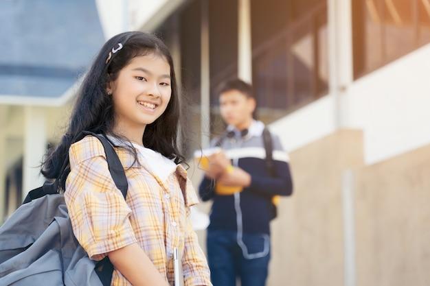 Jonge student tiener meisje middelbare school student uitvoering schooltas bedrijf notebooks met vrienden op achtergrond