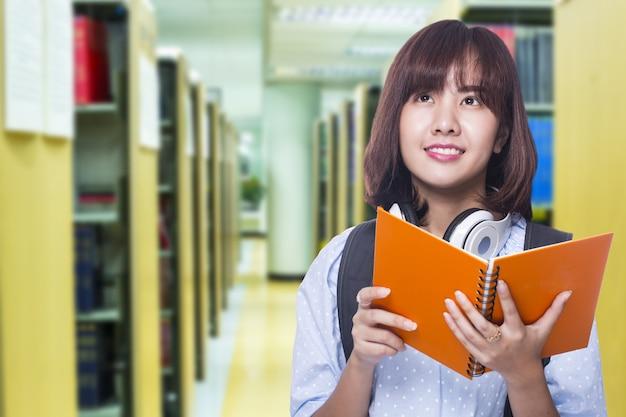 Jonge student vindt leerboek om te zoeken en leert kennis in de universiteitsbibliotheek.