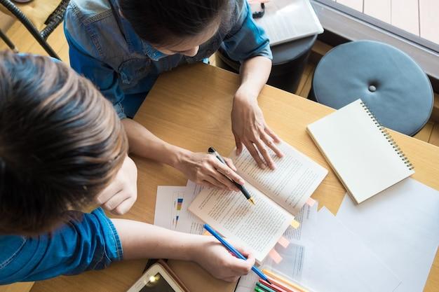 Jonge student voorbereiden op examens en glimlachen. vrouwelijke tutor staande en helpen de jongen leren les