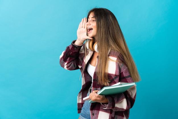 Jonge student vrouw geïsoleerd op blauw schreeuwen met mond wijd open aan de zijkant