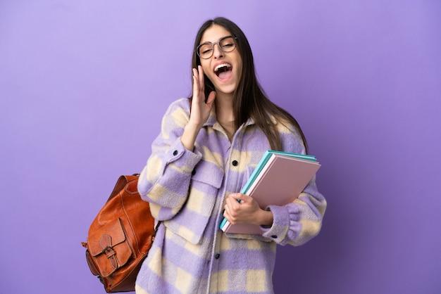 Jonge student vrouw geïsoleerd op paarse achtergrond schreeuwen met mond wijd open