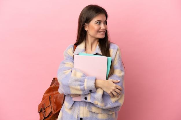 Jonge student vrouw geïsoleerd op roze achtergrond op zoek naar de kant en lachend